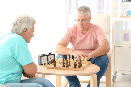 Senior men playing chess at care home