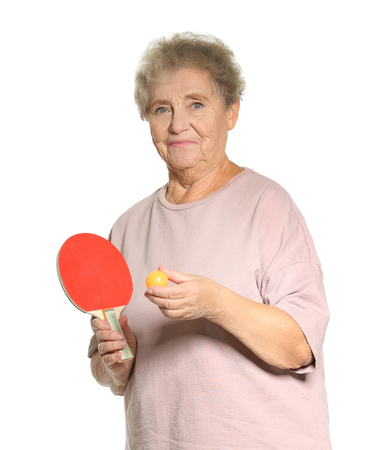 Senior woman playing table tennis against white background