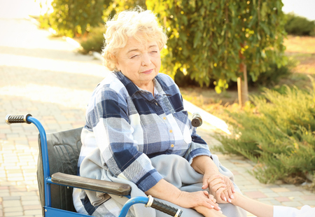 Senior woman in wheelchair holding hands of nurse from care home outdoors Banque d'images