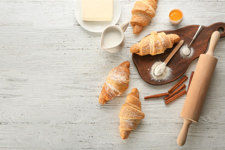 Composition with tasty croissants on white wooden background 免版税图像