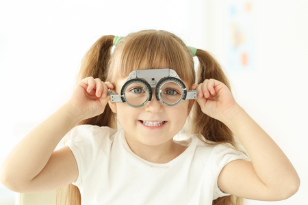 Cute little girl with trial frame in ophthalmologist's office Foto de archivo