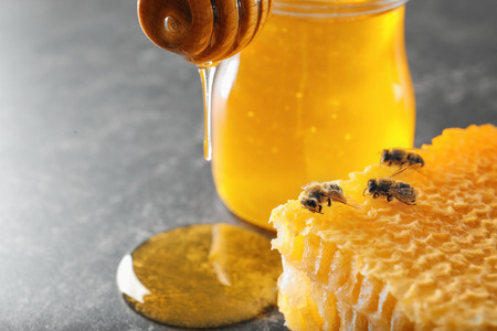 Honeycomb with bees and jar of honey on table