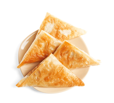 Plate with delicious samosas on white background