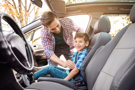Man fastening security belt on his little son in car