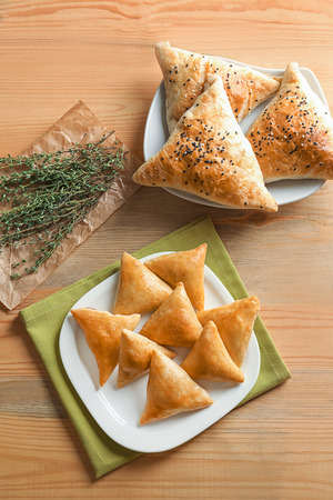 Plates with delicious baked samosas on wooden background