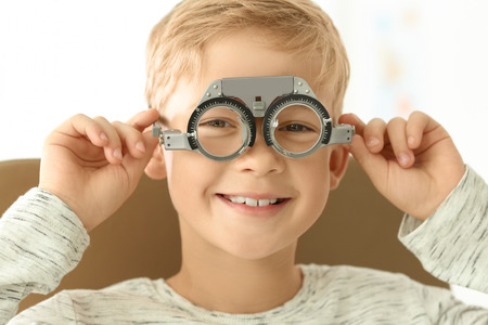 Cute little boy with trial frame in ophthalmologist's office