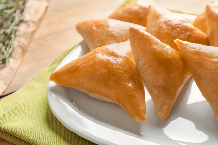 Plate with delicious baked samosas on table, closeup Stock Photo