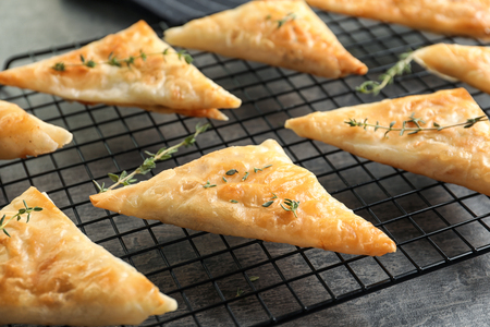 Cooling rack with delicious samosas on table Stock Photo