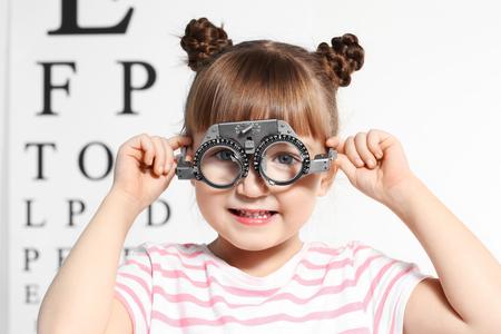 Niña linda con marco de prueba en el consultorio del oftalmólogo