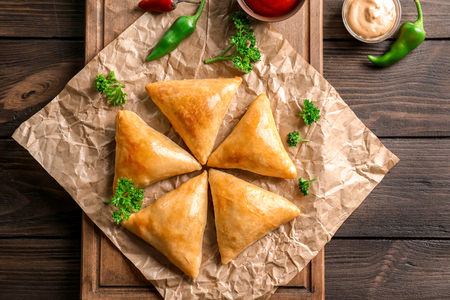 Wooden board with delicious samosas on table Stock Photo