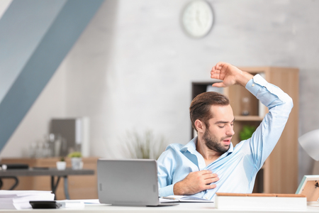 Young man sweating in office Stock Photo