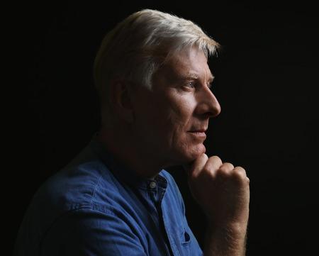Portrait of thoughtful mature man on dark background