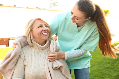 Senior woman and young caregiver in park