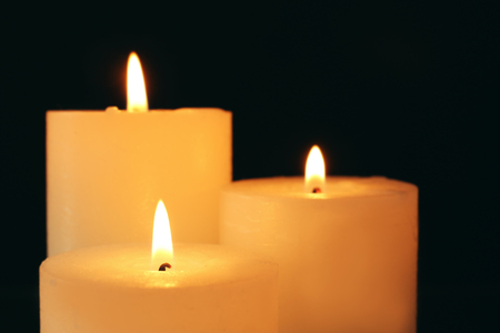 Wax candles burning in darkness, closeup