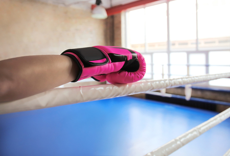 Frau im Boxhandschuh am Ring im Fitnessstudio