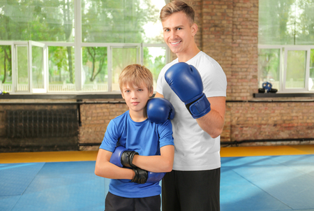 Little boy with trainer in boxing gloves indoors Stock fotó
