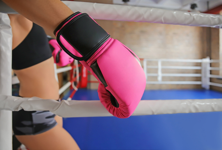 Woman in boxing gloves on ring in gym