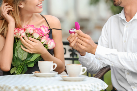 Young man with engagement ring making proposal of marriage to his girlfriend in cafe