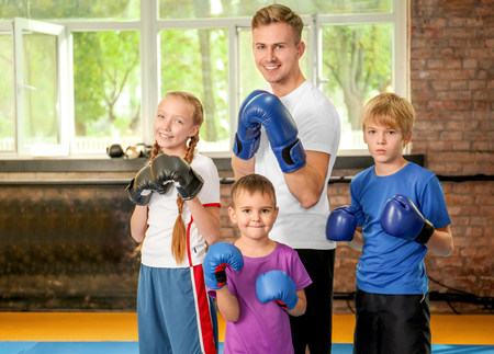 Little children in boxing gloves with trainer indoors