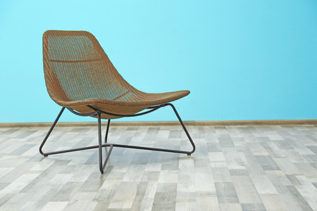 Comfortable armchair on blue wall background
