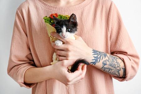 Woman holding little funny kitten in lavash, closeup Archivio Fotografico