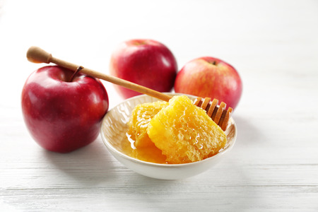 Honeycomb in bowl and apples on wooden table Stock Photo