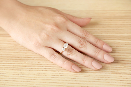 Woman's hand with beautiful engagement ring on table
