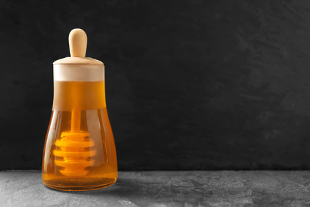 Aromatic honey in glass jar on table against dark background Stok Fotoğraf