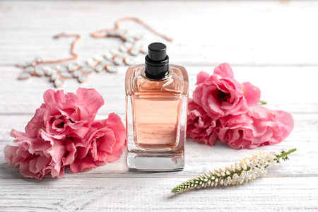 Bottle of perfume and fresh flowers on wooden background