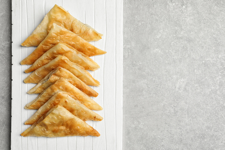 White wooden board with delicious samosas on light background