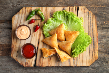 Wooden board with delicious meat samosas on table Reklamní fotografie