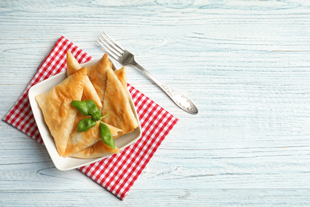 Bowl with delicious samosas on table