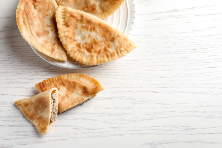 Plate with delicious meat samosas on light background