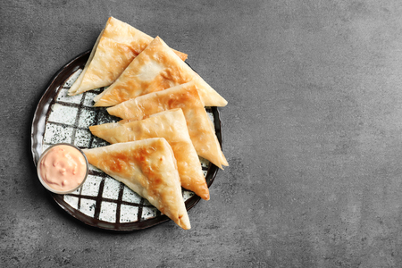 Plate with delicious samosas and sauce on grey background