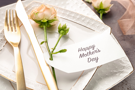 Elegant table layout for dinner with flowers and greeting card Stock Photo - 111786812