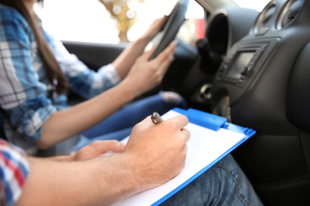 Istruttore di guida che annota i risultati dell'esame, primo piano