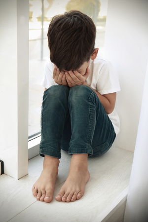 Little sad boy crying at home. Abuse of children concept