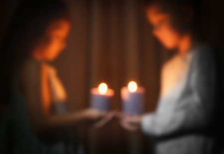 Blurred view of little children holding burning candles in darkness Imagens