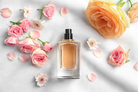 Flacon de parfum avec des fleurs sur un tissu léger