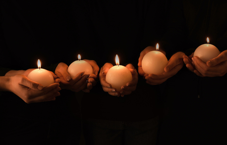 Young people with burning candles in darkness