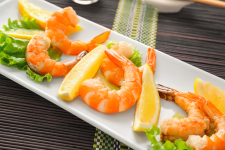 Delicious shrimps with lettuce and lemon on plate 写真素材