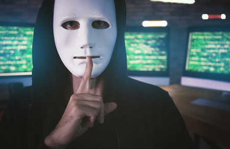 Masked hacker in dark room with computers. Threat of cyber attack