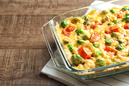 Baking dish with yummy brussel sprouts casserole on wooden table