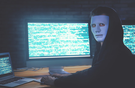 Masked hacker using computer in dark room. Threat of cyber attack Stock Photo - 111969881