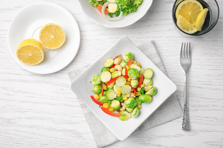Plate of tasty salad with Brussels sprouts on table Stock Photo