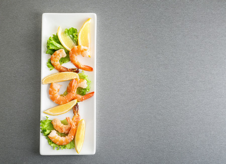 Delicious shrimps with lettuce and lemon served on table 版權商用圖片