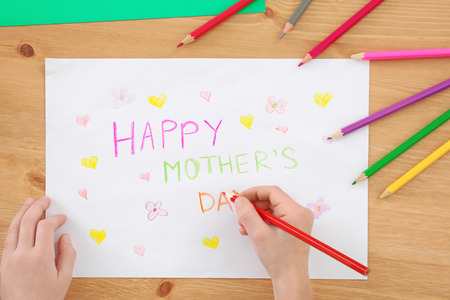 Little girl preparing greeting card for her mommy on Mothers Day at table
