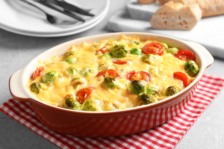 Baking dish with yummy brussel sprouts casserole on table