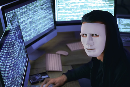 Masked hacker using computer in dark room. Threat of cyber attack Stock Photo