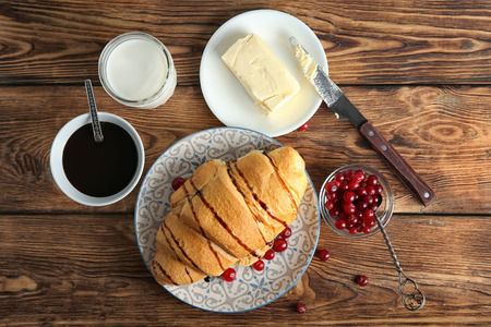 Composition with yummy fresh croissant on wooden table Imagens